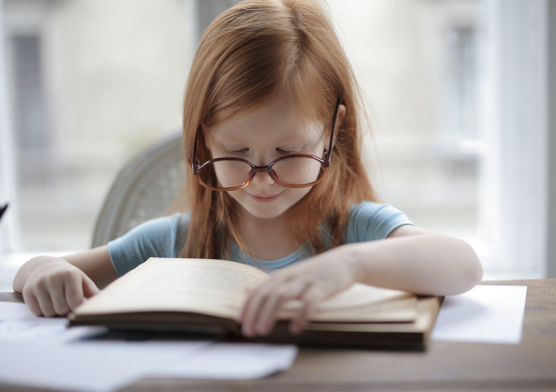 girl in blue short sleeve t shirt reading book
